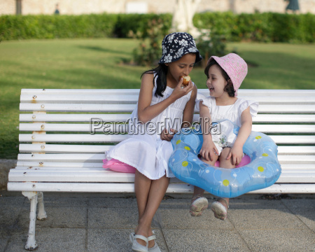 two young girls sitting on bench