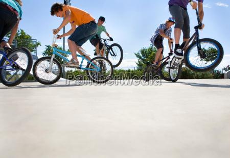 teen boys on bikes jumping