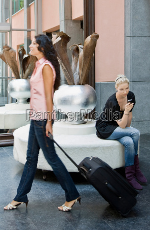 women with luggage and cellular phone