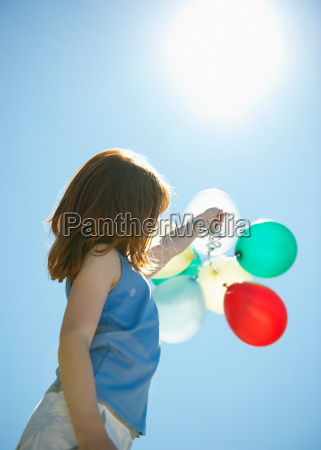 young girl holding balloons into sky