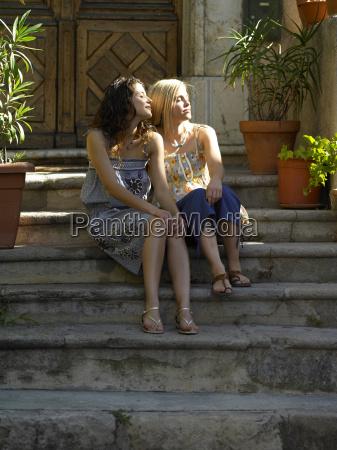 female friends sitting on step