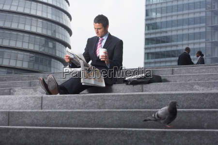 business man reading paper outside