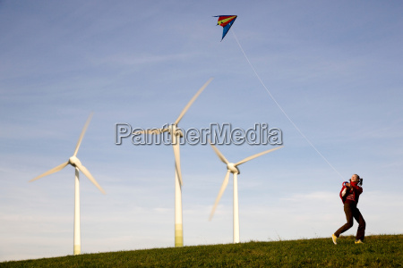 girl flying kite at wind turbines