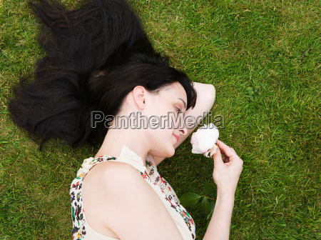 woman laying on grass smelling rose