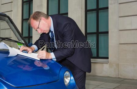 man signing document on car bonnet