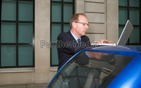 man using laptop on car
