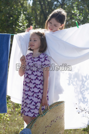 young girls standing by washing line