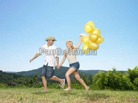 couple running with balloons