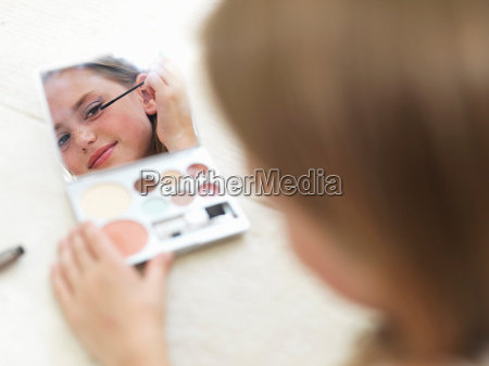 girl in mirror putting on make