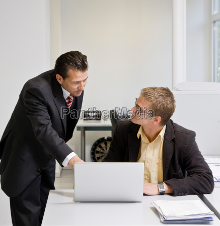 boss looking at laptop with co