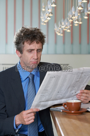 businessman at bar reading paper doubt