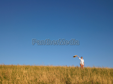 woman waving hat in field