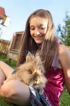 girl playing with rabbit in garden