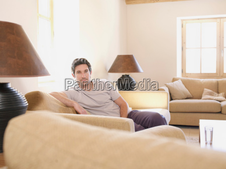 man relaxing on sofa in living