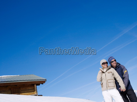man and woman in snow looking