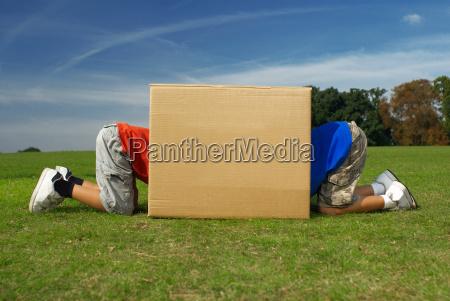two boys crawling into box