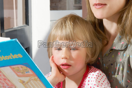 girl on mothers lap reading book