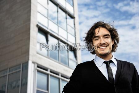 man smiling at camera building behind