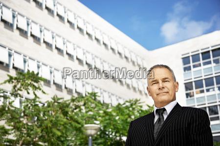 business man standing buildings behind