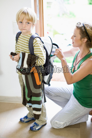 mother getting her son ready for