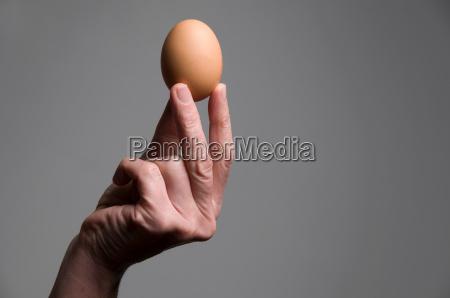 female hand holding an egg
