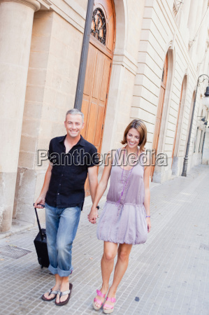 couple with trolly walking along street