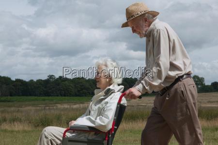 elderly man pushing woman in wheelchair