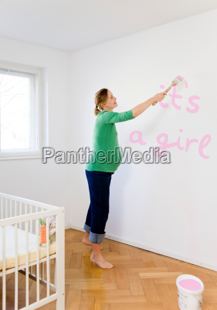 pregnant woman painting nursery