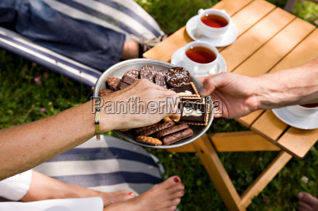 man offering biscuits to senior woman