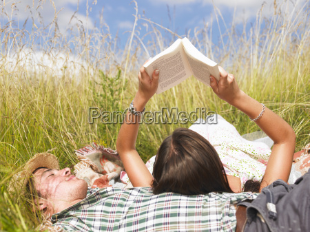 couple lying in field of high