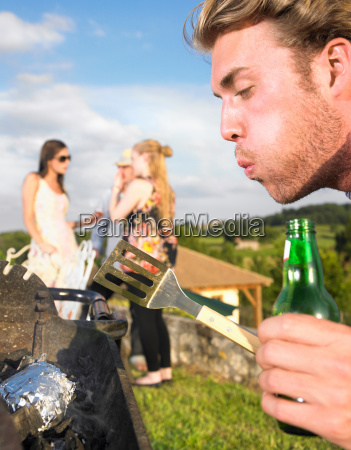 young man tending barbecue