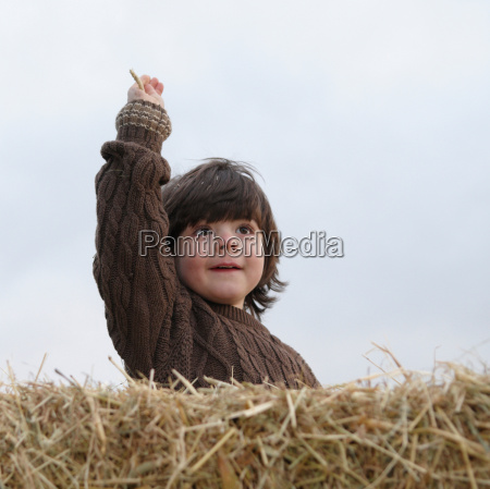 young boy on hay bale
