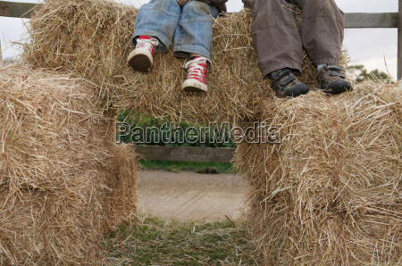 young boys sitting on hay bales