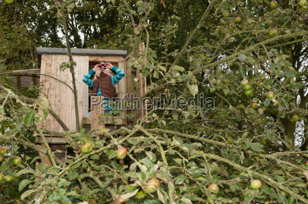 girl with binoculars in treehouse