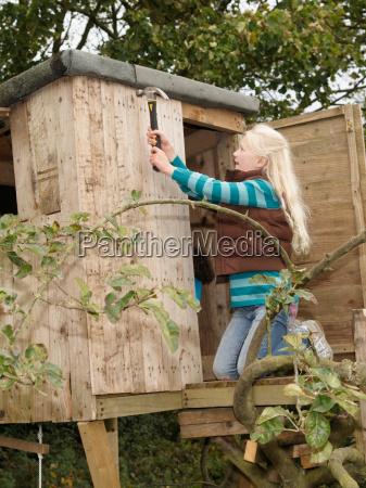 girl mending treehouse