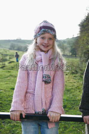 young girl on gate in countryside