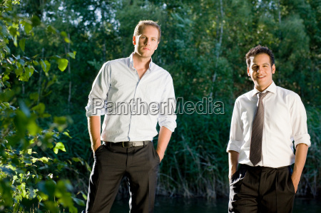 two businessmen standing in nature
