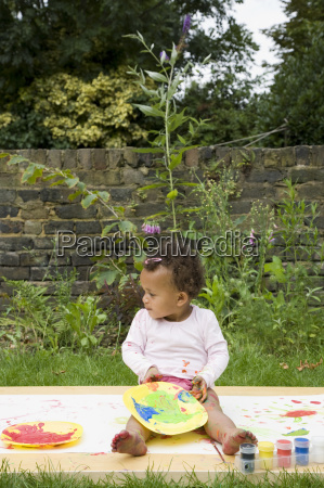 child painting in the garden