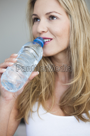 young woman drinking bottle of water