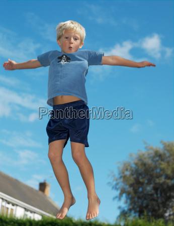 boy 7 playing on trampoline