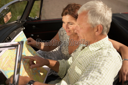 senior couple with car and map