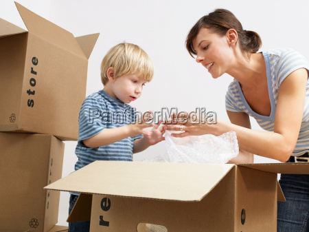 mother and son unpacking moving boxes