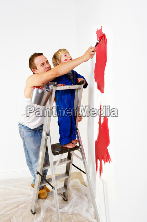 man and toddler boy painting wall