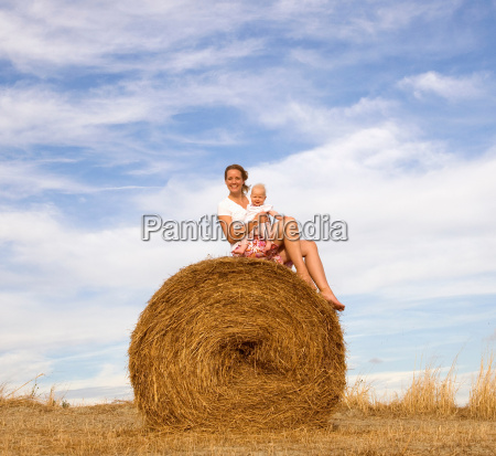 woman holding baby on hay bale
