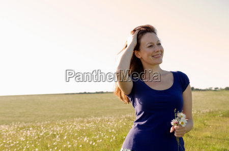 smiling woman holds flowers in meadow