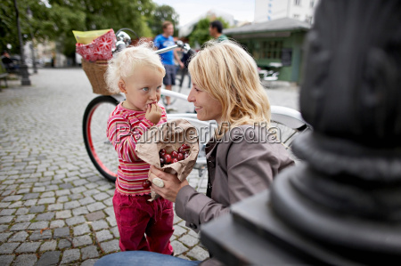 little girl and mother eating cherries