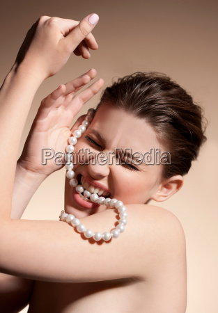 nude woman biting string of pearls