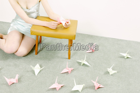 woman making origami swans