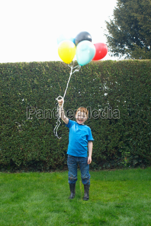 smiling boy holding bunch of balloons