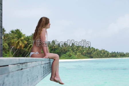 woman sitting on deck overlooking beach
